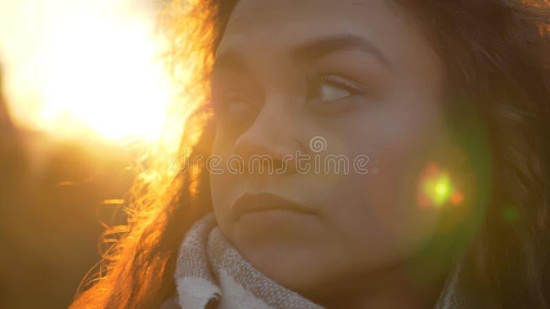 Retrato do close-up no perfil da menina caucasiano encaracolado-de cabelo que olha para um lado atentamente no parque outonal foto de stock