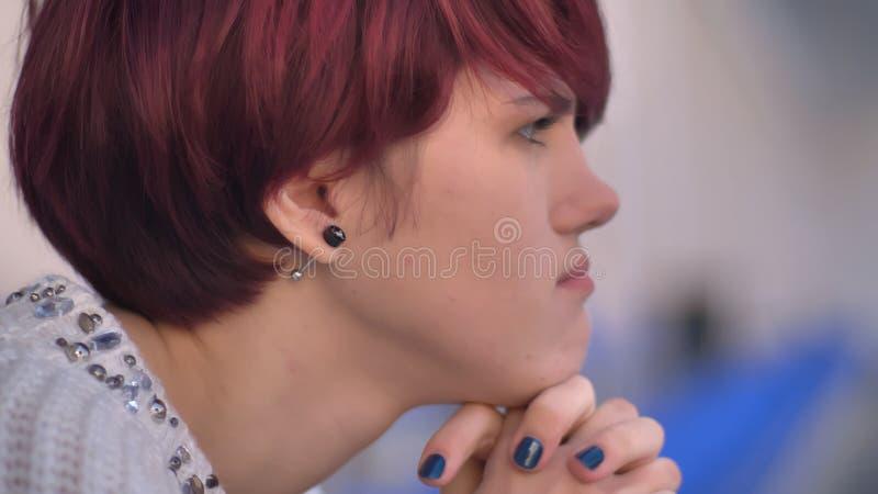 Retrato do close-up no perfil da menina cor-de-rosa-de cabelo caucasiano nova concentrada que senta-se no estádio e no pensamento imagens de stock