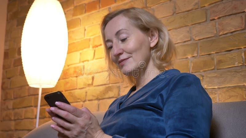 Retrato do close-up no perfil da senhora caucasiano superior alegre que olha no smartphone com interesse na casa acolhedor foto de stock