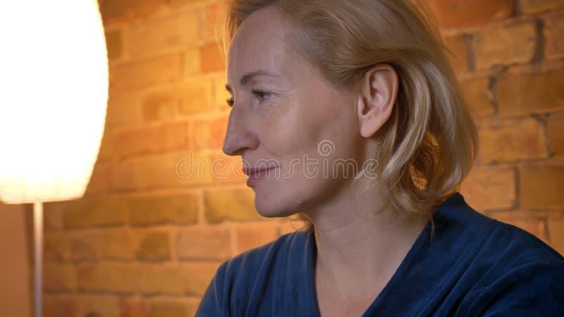 Retrato do close-up no perfil da senhora caucasiano superior que olha pensativamente leftwards na atmosfera de casa acolhedor fotografia de stock