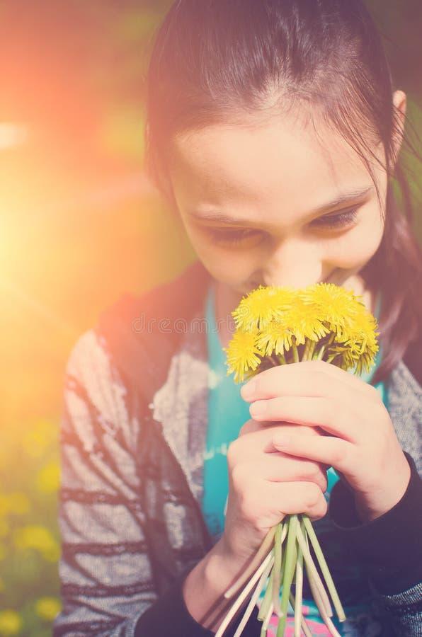 Retrato do close-up do ramalhete de sorriso da terra arrendada da moça das flores nas mãos Menina com dentes-de-leão amarelos Car foto de stock royalty free