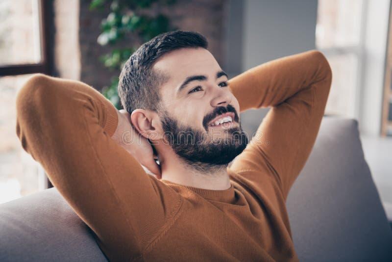 Retrato do close-up do seu ele queolha o indivíduo seguro animador alegre farpado atrativo que senta-se na despesa do divã imagem de stock