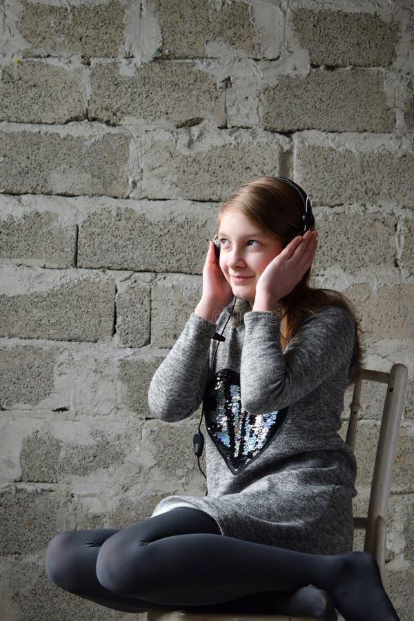 Retrato do conceito de um adolescente feliz amigável agradável nos fones de ouvido que escuta a música A moça está sentando-se em fotos de stock royalty free