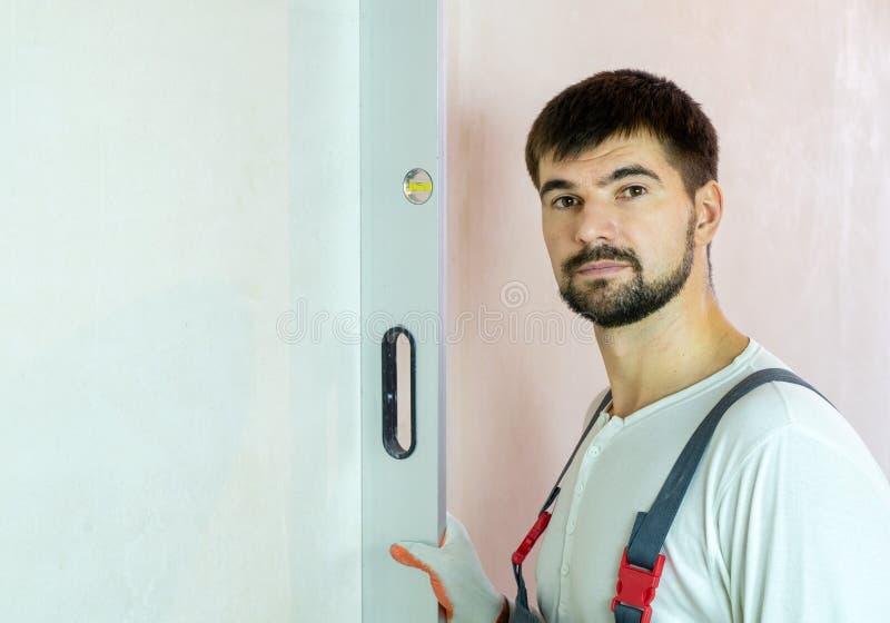 Retrato do construtor farpado com nível de bolha contra a parede vazia com espaço livre fotos de stock royalty free