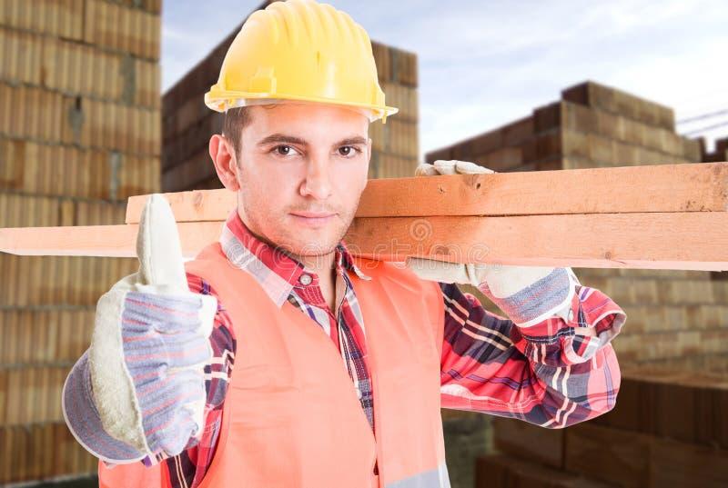 Retrato do construtor novo que mostra o polegar acima do sinal foto de stock royalty free