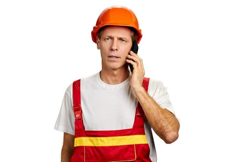 Retrato do construtor que fala no telefone fotos de stock