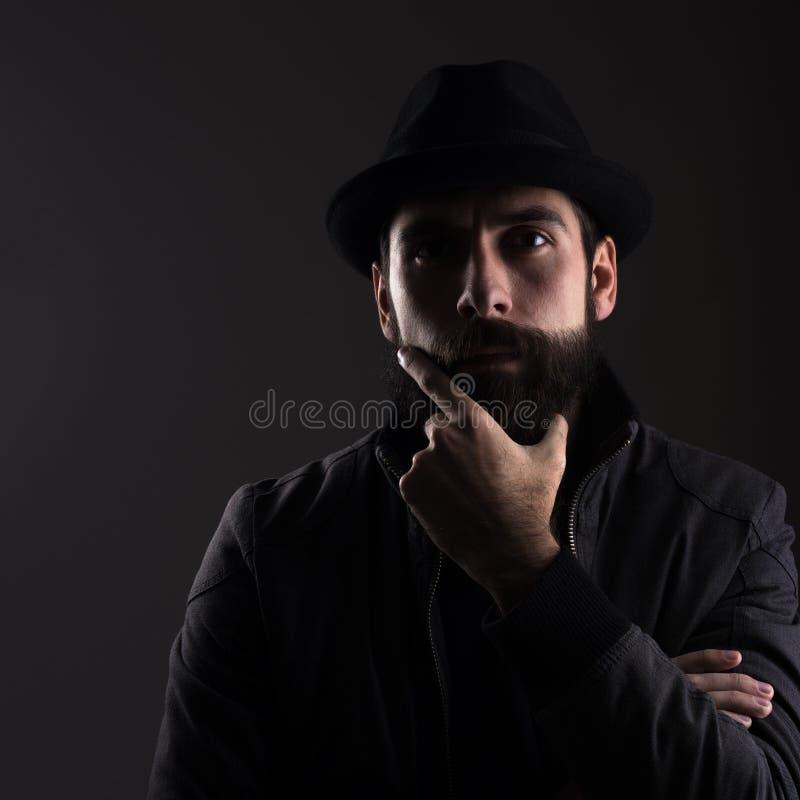 Retrato do contraste alto do pensamento vestindo do chapéu negro do homem farpado sério fotos de stock