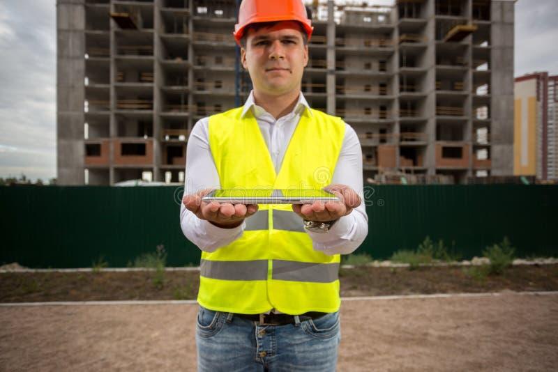 Retrato do coordenador de construção masculino que guarda a tabuleta digital Aperfeiçoe introduzindo sua própria imagem na tela d imagem de stock