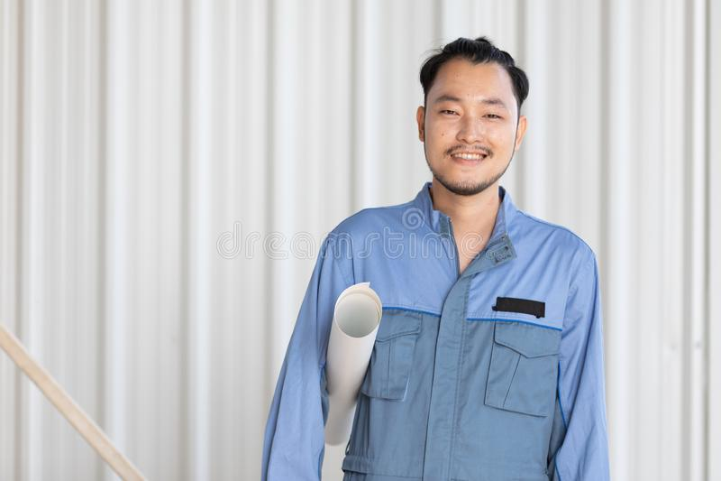 Retrato do coordenador masculino com autoconfiança e maneira amigável, guardando o papel de rolo fotografia de stock royalty free