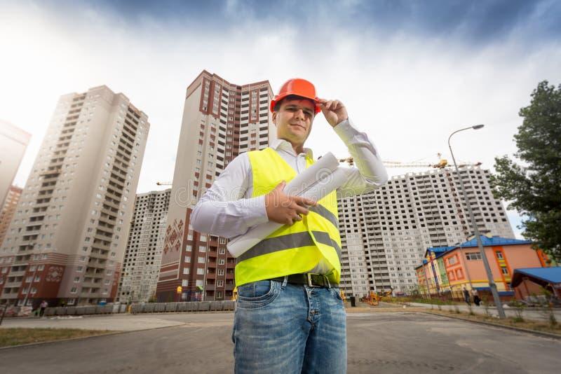Retrato do coordenador masculino de sorriso que veste o capacete plástico vermelho no terreno de construção imagens de stock