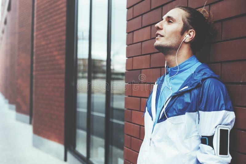 Retrato do corredor que está na rua perto da parede e do descanso de tijolo, na fita com telefone celular e nos fones de ouvido c fotos de stock royalty free
