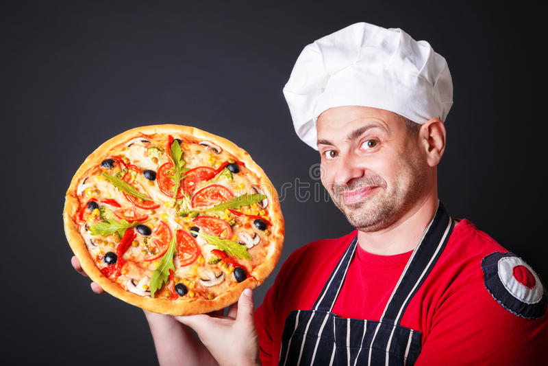 Retrato do cozinheiro atrativo feliz com uma pizza nas mãos imagem de stock