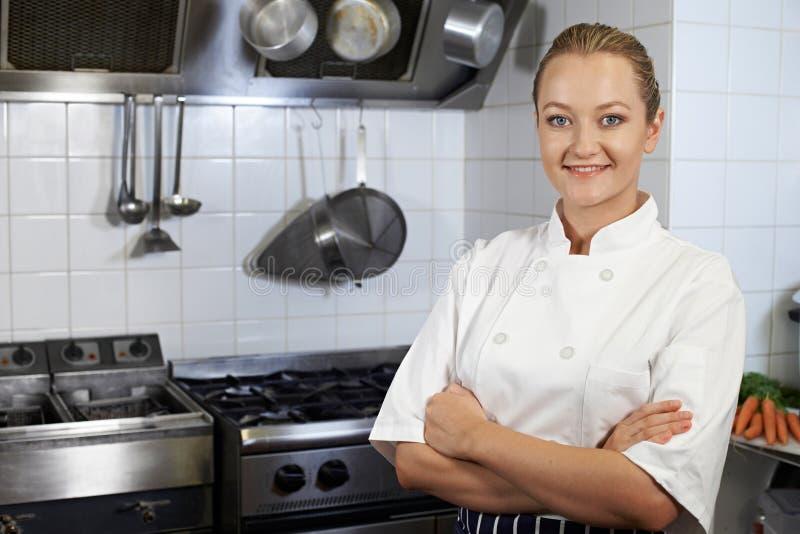 Retrato do cozinheiro chefe fêmea Standing In Kitchen fotografia de stock