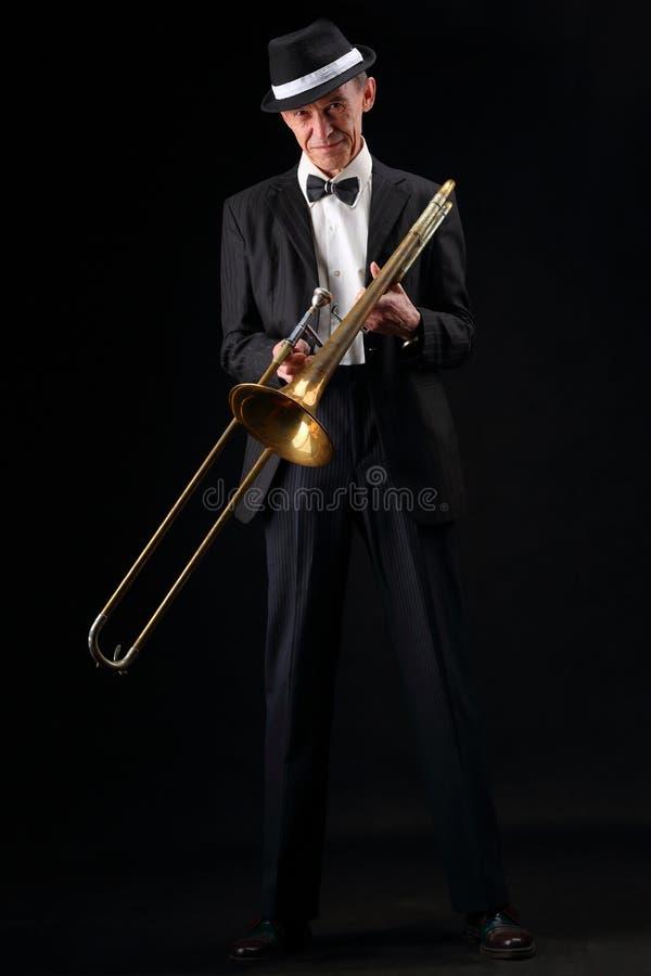 Retrato do crescimento de um músico idoso com um trombone imagem de stock