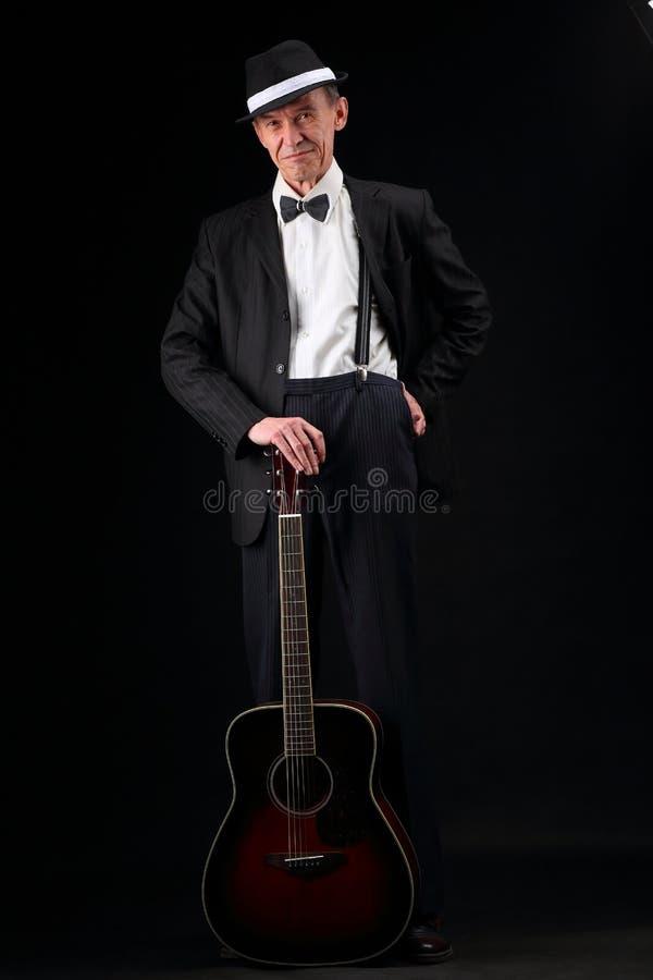 Retrato do crescimento de um músico idoso com uma guitarra fotografia de stock royalty free