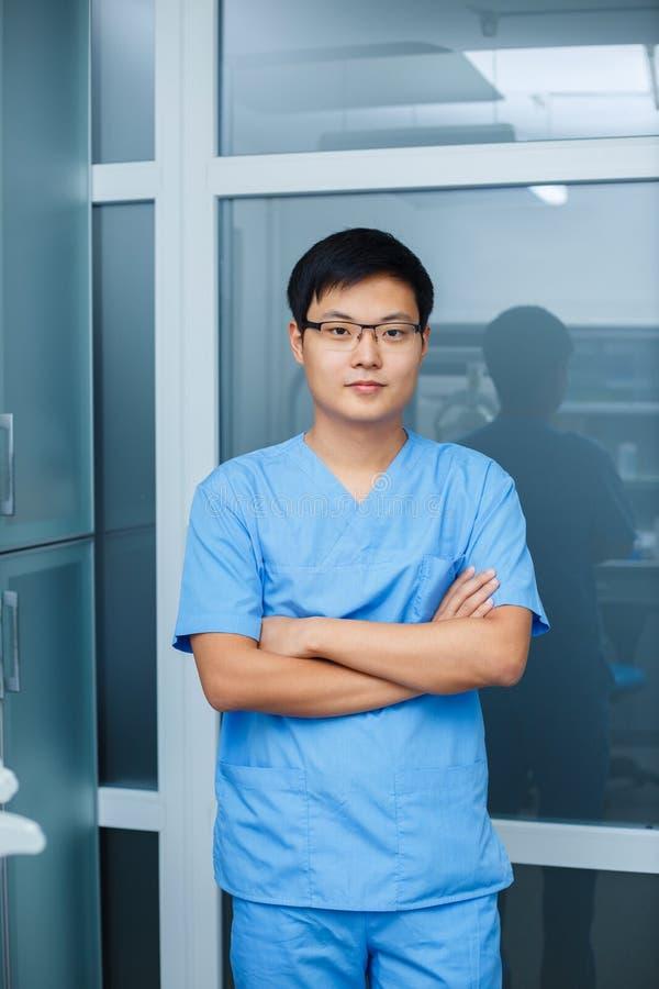 Retrato do dentista asiático novo do homem na clínica Odontologia, mim imagens de stock