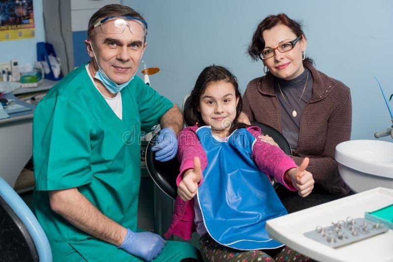Retrato do dentista e da moça superiores com sua mãe na primeira visita dental no escritório dental foto de stock