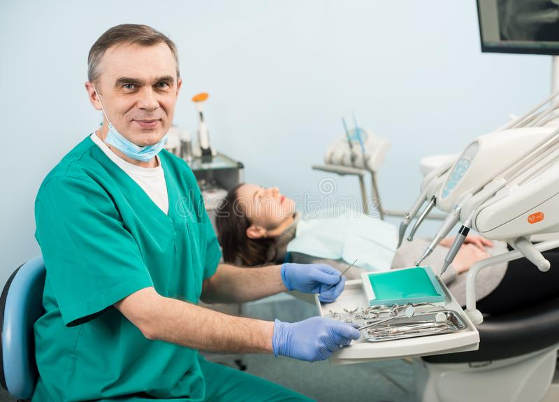 Retrato do dentista masculino considerável com dispositivos dentais na clínica dental imagem de stock