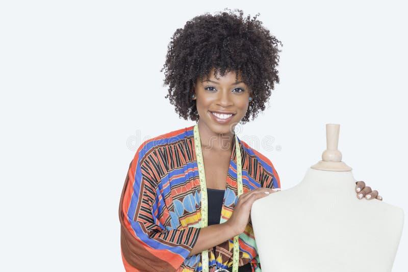 Retrato do desenhador de moda fêmea afro-americano com o manequim do alfaiate sobre o fundo cinzento imagem de stock royalty free