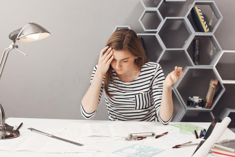Retrato do desenhista autônomo fêmea considerável de cabelo escuro novo nas mãos de espalhamento da camisa ocasional listrada, se imagem de stock