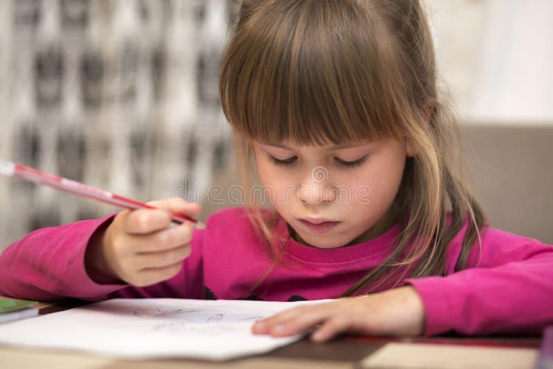 Retrato do desenho sério pequeno bonito bonito da menina da criança com o lápis no papel no fundo borrado Educação da arte, facul fotos de stock royalty free