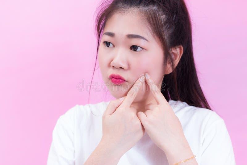 Retrato do desgaste asiático novo bonito do cabelo preto da mulher um t-shirt branco que espreme espinhas em sua cara Verifica su fotos de stock