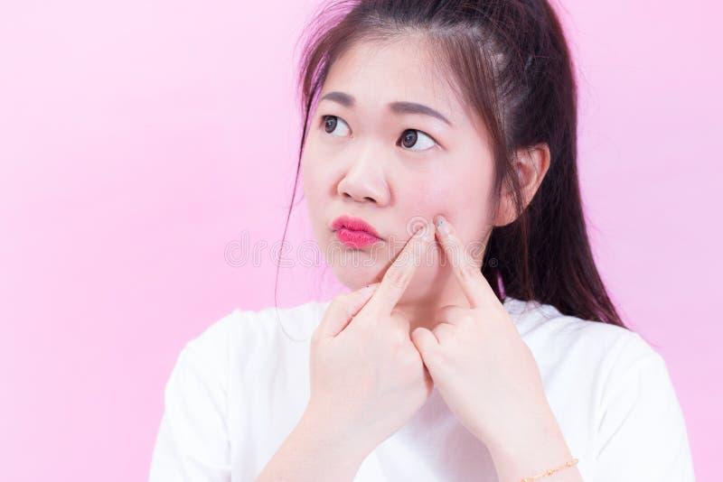 Retrato do desgaste asiático novo bonito do cabelo preto da mulher um t-shirt branco que espreme espinhas em sua cara Verifica su imagem de stock