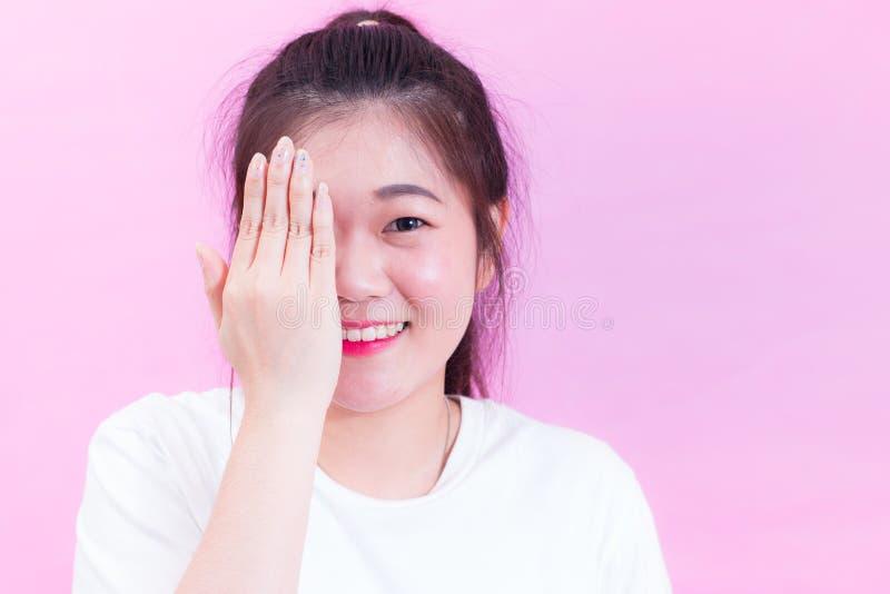 Retrato do desgaste asiático novo bonito do cabelo preto da mulher uma coberta branca do t-shirt com mãos seus olho e sorriso imagens de stock