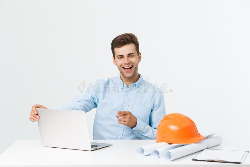 Retrato do designer de interiores ou do coordenador masculino novo que sorriem ao sentar-se em sua tabela do escritório imagens de stock