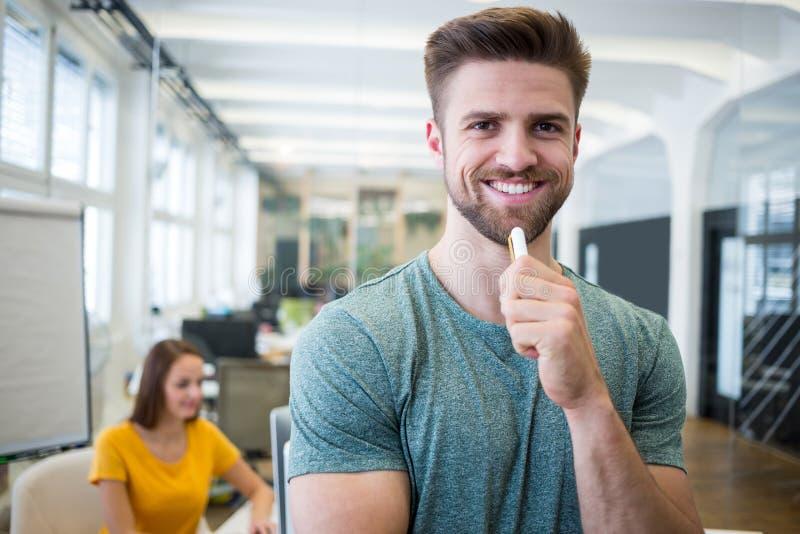 Retrato do designer gráfico de sorriso que está com pena fotografia de stock royalty free