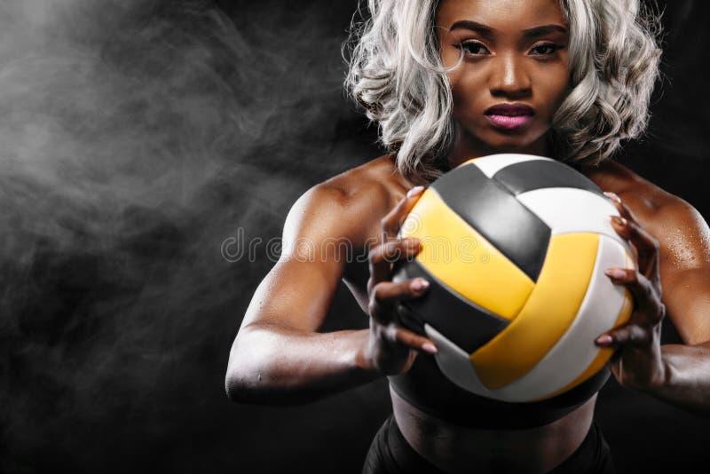 Retrato do desportista afro-americano, jogador de voleibol da praia com uma bola Jovem mulher do ajuste na bola da terra arrendad fotos de stock