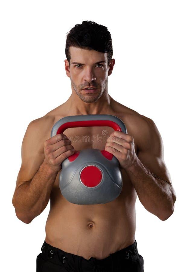 Retrato do desportista descamisado que exercita com sino da chaleira fotografia de stock royalty free