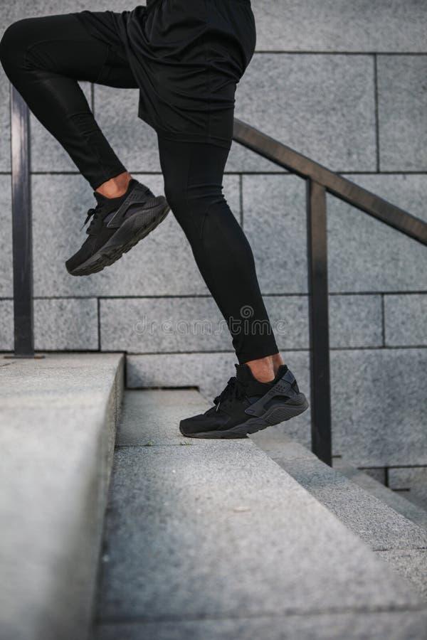 Retrato do desportista que corre acima escadas imagens de stock