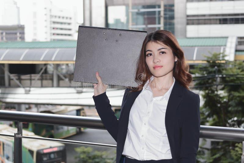 Retrato do dobrador asiático novo atrativo do documento da terra arrendada da mulher do secretário no escritório exterior imagens de stock royalty free