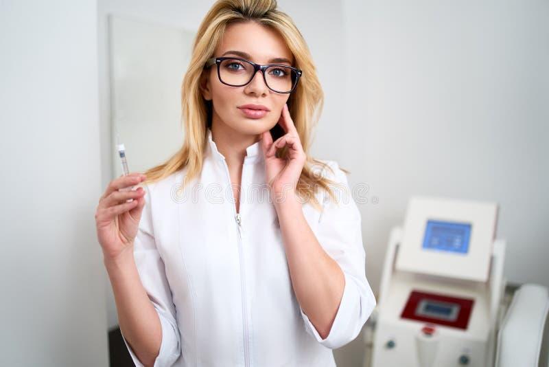 Retrato do doutor atrativo novo do esteticista com seringa à disposição Cosmetologist que guarda ferramentas médicas Practician d foto de stock