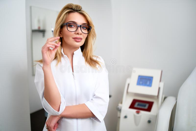 Retrato do doutor atrativo novo do esteticista com seringa ? disposi??o Cosmetologist que guarda ferramentas m?dicas Practician d fotos de stock