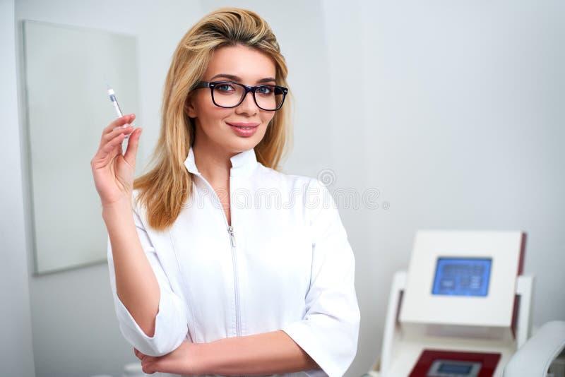 Retrato do doutor atrativo novo do esteticista com seringa ? disposi??o Cosmetologist que guarda ferramentas m?dicas Practician d imagem de stock