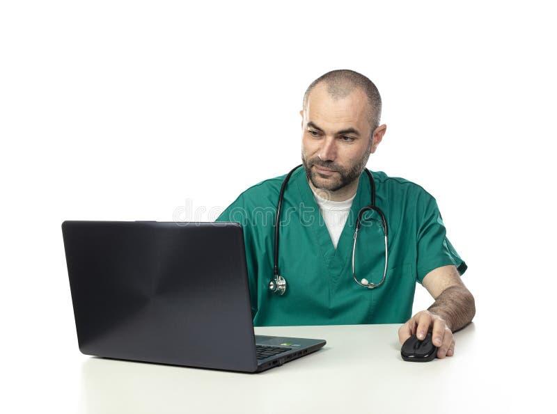 Retrato do doutor caucasiano que veste o uniforme verde, trabalho com portátil imagem de stock royalty free