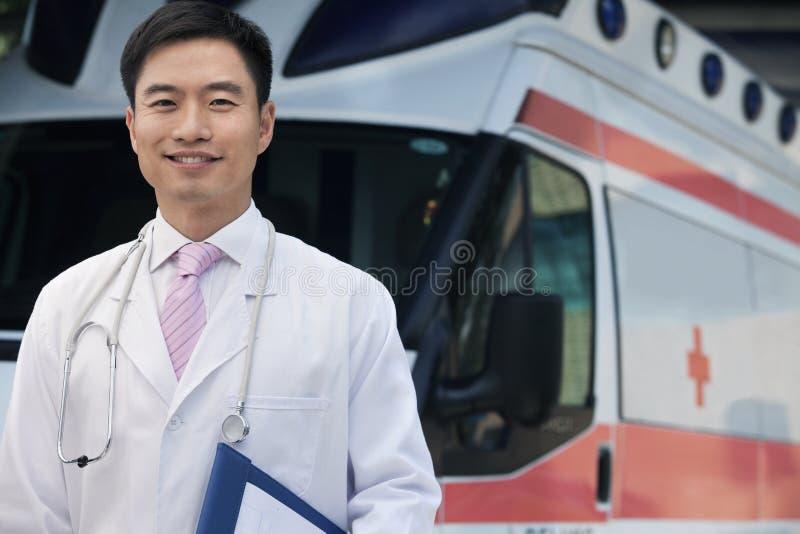 Retrato do doutor de sorriso que guarda a prancheta na frente de uma ambulância fotografia de stock