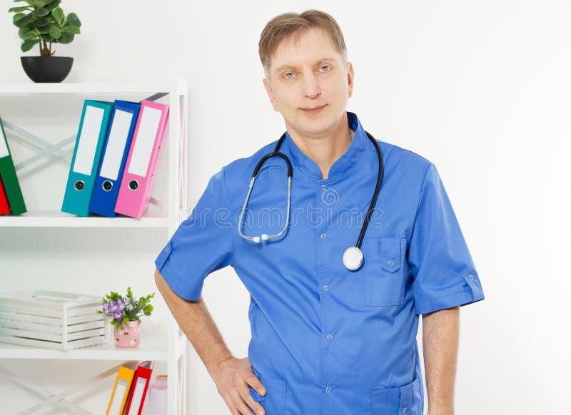 Retrato do doutor de sorriso que levanta com o escrit?rio, est? vestindo um estetosc?pio, o espa?o da c?pia para o logotipo ou o  imagens de stock