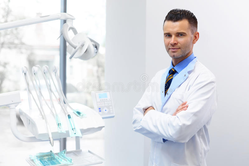 Retrato do doutor do dentista Homem novo em seu local de trabalho Clin dental imagem de stock