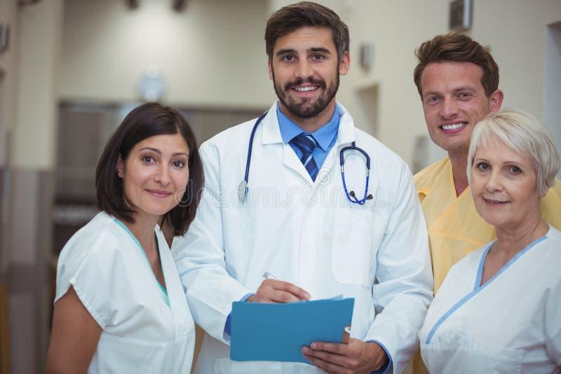 Retrato do doutor e da enfermeira que têm a discussão sobre o arquivo no corredor fotografia de stock