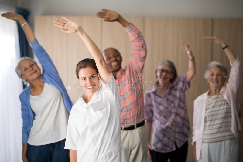 Retrato do doutor e dos sêniores fêmeas de sorriso que exercitam com os braços aumentados imagem de stock