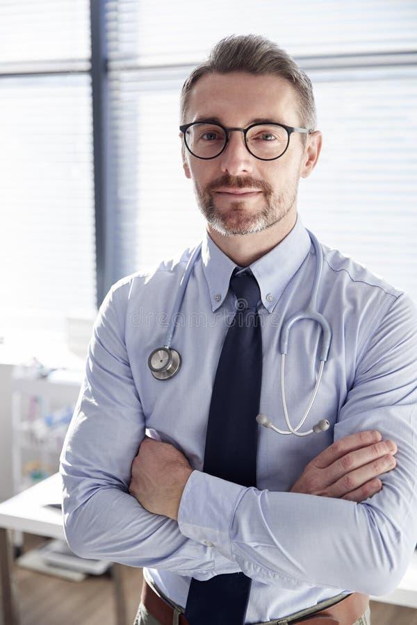 Retrato do doutor masculino maduro de sorriso With Stethoscope Standing pela mesa no escritório imagem de stock royalty free
