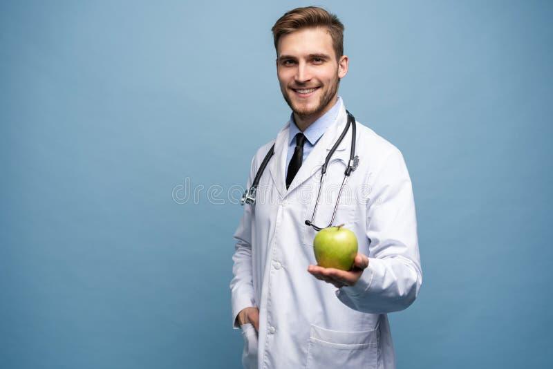 Retrato do doutor masculino novo que guarda a maçã verde Isolado na luz - azul imagens de stock