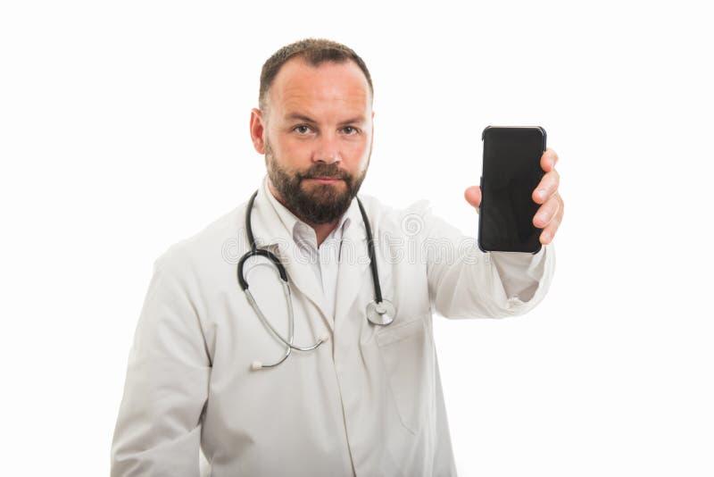 Retrato do doutor masculino que mostra o smartphone à câmera fotos de stock royalty free