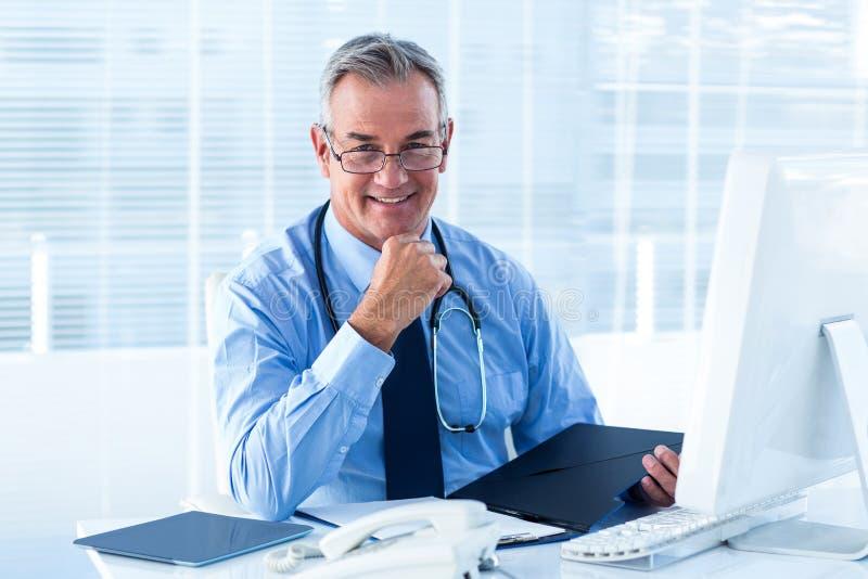 Retrato do doutor masculino que senta-se na mesa no hospital fotos de stock royalty free