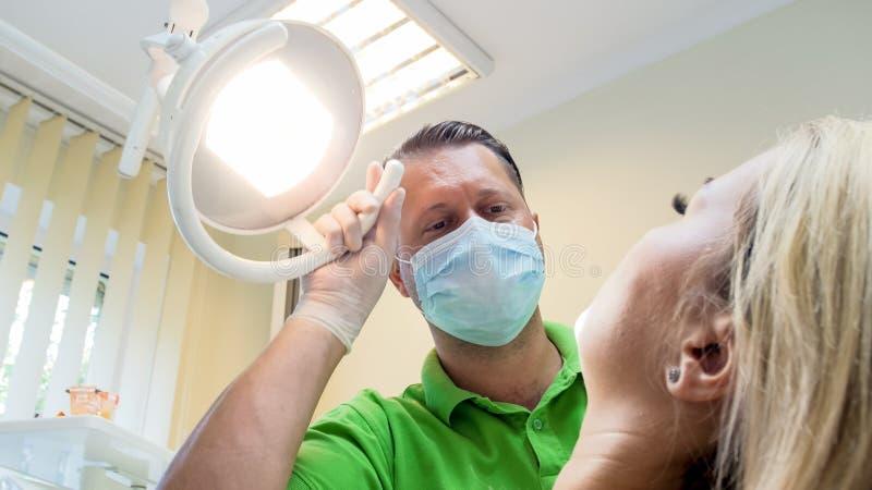 Retrato do doutor masculino que usa a lâmpada para inspecionar o paciente fêmea imagem de stock royalty free