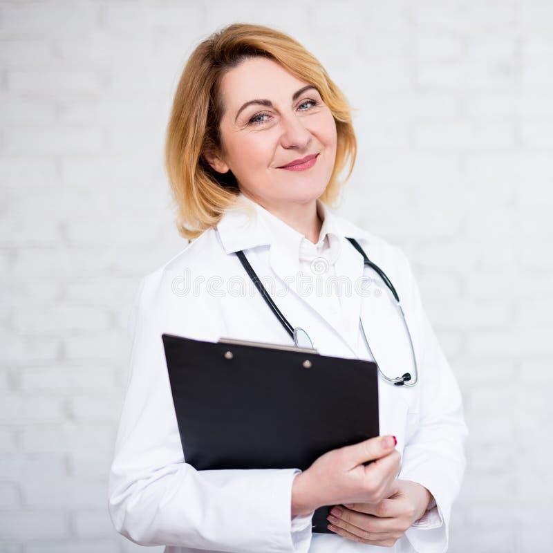 Retrato do doutor ou da enfermeira fêmea madura com a prancheta sobre a parede branca imagens de stock royalty free