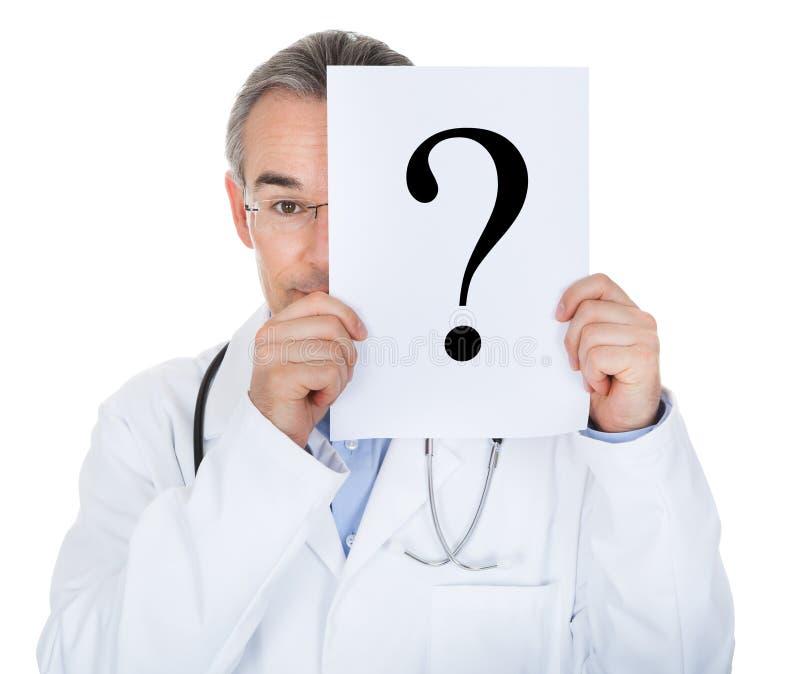 Retrato do doutor que guarda de papel com ponto de interrogação imagem de stock